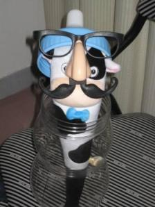 The cow stick in glasses sitting in a baby bottle piggy bank